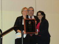 Nancy Daniels with Carlos Martinez & Judge Angelica Zayas holding award
